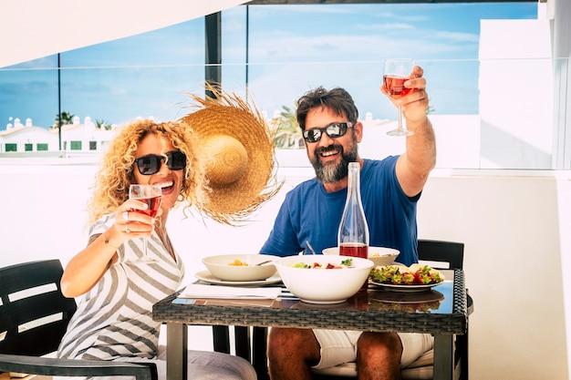 Szczęśliwi weseli ludzie para w średnim wieku piękna kobieta i mężczyzna uśmiechają się i opiekują się czerwonym winem jedząc razem na świeżym powietrzu w restauracji lub domu na tarasie z błękitnym niebem na powierzchni