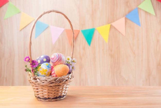 Szczęśliwi wielkanocnego dnia kolorowi jajka, kwiaty w koszu i królik zamazujący świętują przyjęcie flaga z kopii przestrzenią