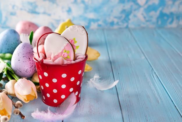 Szczęśliwi wielkanocni piernikowi ciastek jajka z wiadrem i tulipanami z kolorowymi jajkami