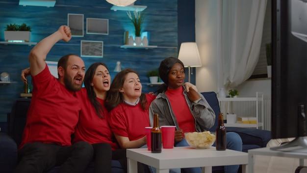 Szczęśliwi wieloetniczni przyjaciele oglądający mecz piłki nożnej podczas zawodów sportowych