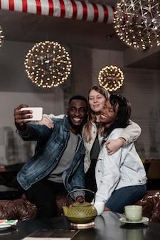 Szczęśliwi wielokulturowi przyjaciele przy selfie