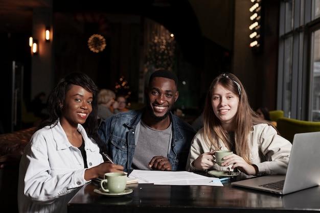Szczęśliwi wielokulturowi przyjaciele w coffeeshopie