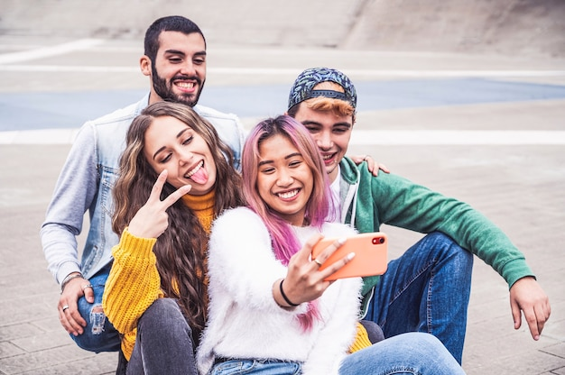 Szczęśliwi wielorasowi nastoletni przyjaciele uśmiechają się podczas robienia selfie na ulicy miasta - nowa koncepcja normalnego stylu życia z młodymi studentami, którzy bawią się razem w pobliżu kampusu