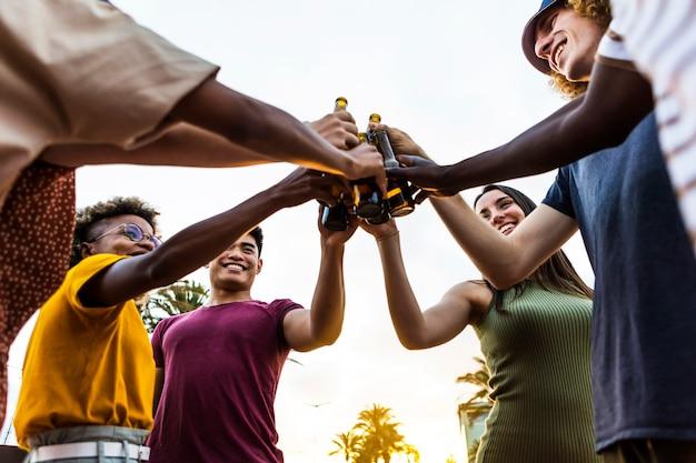 Szczęśliwi wielorasowi przyjaciele bawią się podczas relaksu o zachodzie słońca