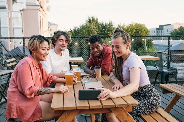 Szczęśliwi wielorasowi przyjaciele komunikujący się na czacie wideo w kawiarni na świeżym powietrzu