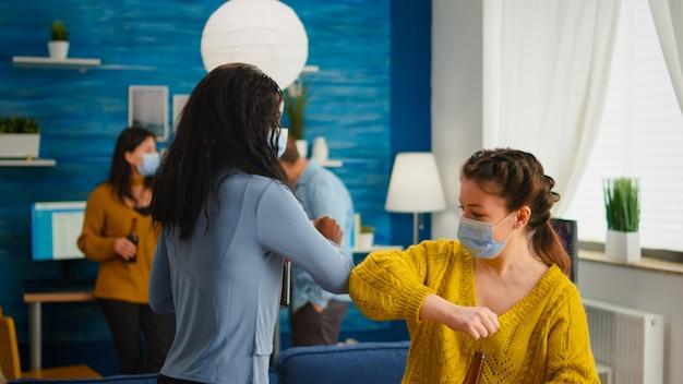 Szczęśliwi wielorasowi przyjaciele w masce ochronnej dotykającej łokcia utrzymujący dystans społeczny, przytulający się nawzajem do spotkania na imprezę w salonie. osoby towarzyskie podczas epidemii covid 19