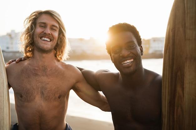 Szczęśliwi wielorasowi surferzy bawią się na plaży po surfingu - skoncentruj się na twarzach