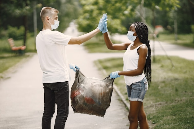 Szczęśliwi wolontariusze przybijają sobie piątkę po wykonaniu zadań. african american dziewczyna i europejski chłopak.