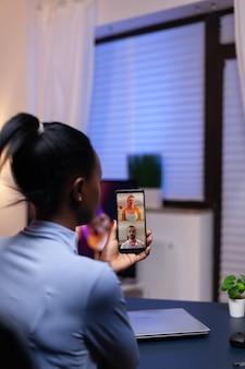 Szczęśliwi współpracownicy rozmawiają i konsultują się podczas wideokonferencji na smartfonie. zajęty pracownik przy użyciu nowoczesnych technologii sieci bezprzewodowej robi nadgodziny do pracy.