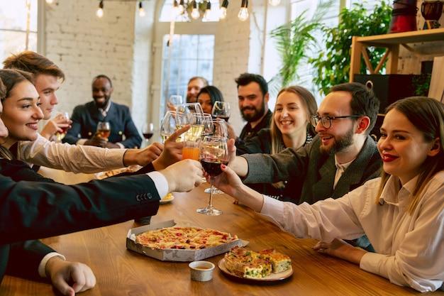 Szczęśliwi współpracownicy świętują podczas imprezy firmowej i imprezy firmowej. młodzi ludzie rasy kaukaskiej w strojach biznesowych doping, śmiejąc się. pojęcie kultury biurowej, pracy zespołowej, przyjaźni, wakacji, weekendu.