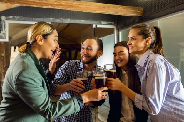 Szczęśliwi współpracownicy świętujący imprezę firmową po napiętym dniu pracy wyglądają na zachwyconych przyjaźnie