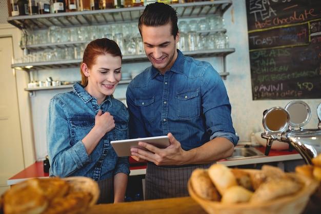 Szczęśliwi współpracownicy używa pastylka komputer przy kawiarnią