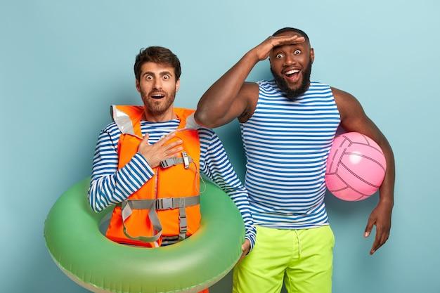 Szczęśliwi, zaskoczeni, różnorodni młodzi mężczyźni ubrani w marynarskie koszulki i szorty trzymają piłkę plażową