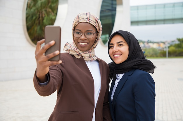 Szczęśliwi żeńscy biurowi przyjaciele bierze selfie outside