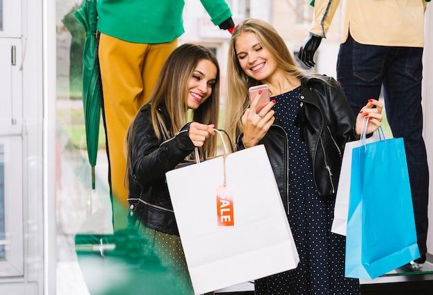 Szczęśliwi żeńscy przyjaciele cieszy się zakupy blisko nadokiennego pokazu