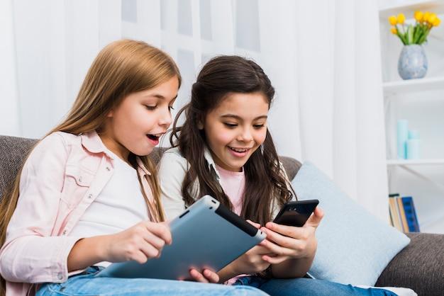 Szczęśliwi żeńscy przyjaciele siedzi na kanapie używać cyfrową pastylkę i telefon komórkowego