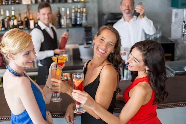 Szczęśliwi żeńscy przyjaciele trzyma szkło koktajl przy baru kontuarem