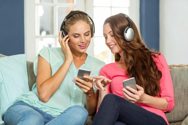 Szczęśliwi żeńscy przyjaciele trzyma telefony komórkowe