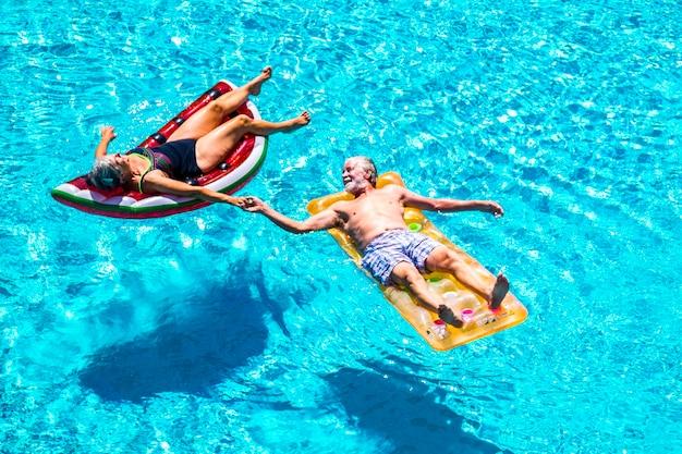 Szczęśliwi zrelaksowani ludzie kaukaska starsza para dorosłych biorących ręce położyła się z modnymi kolorowymi lilo na basenie z niebieską wodą podczas letnich wakacji - ciesząc się aktywnym stylem życia na emeryturze