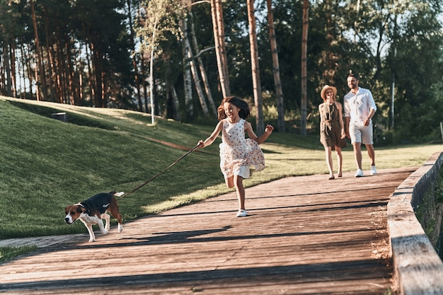 Szczęśliwie być razem. pełna długość uroczej małej dziewczynki biegającej z psem i uśmiechającej się, podczas gdy jej rodzice idą za nią