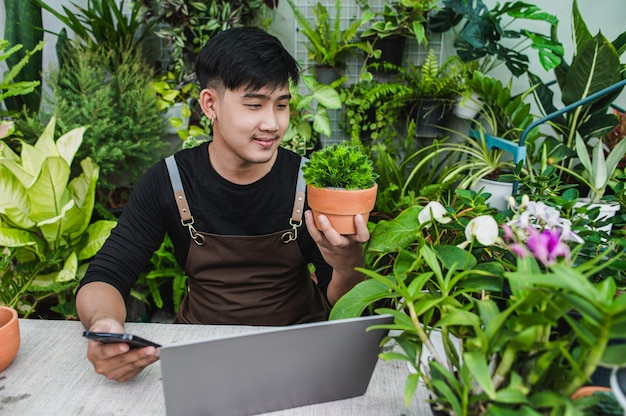 Szczęśliwie mężczyzna ogrodnik używa smartfona i laptopa podczas samouczka online na temat planów doniczkowych w sklepie