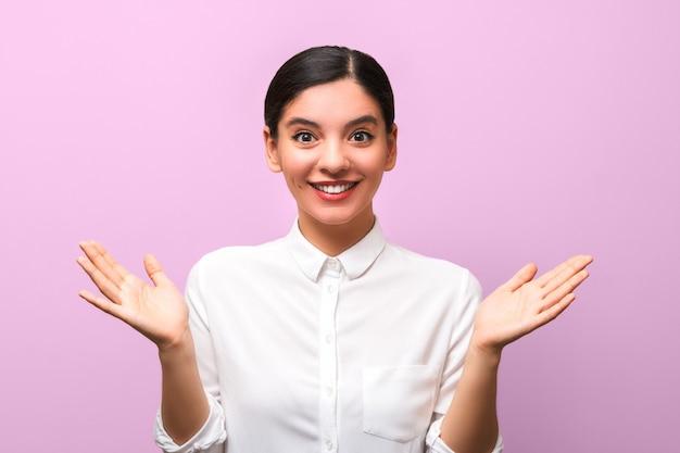 Szczęśliwie podekscytowana atrakcyjna kobieta w białej koszuli i czerwonych ustach z rękami do góry i otwartymi dłońmi.