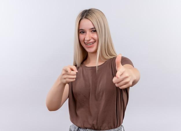 Szczęśliwie uśmiechnięta młoda blondynka w aparatach ortodontycznych wskazując i pokazując kciuk w górę na odosobnionej białej przestrzeni z miejsca na kopię