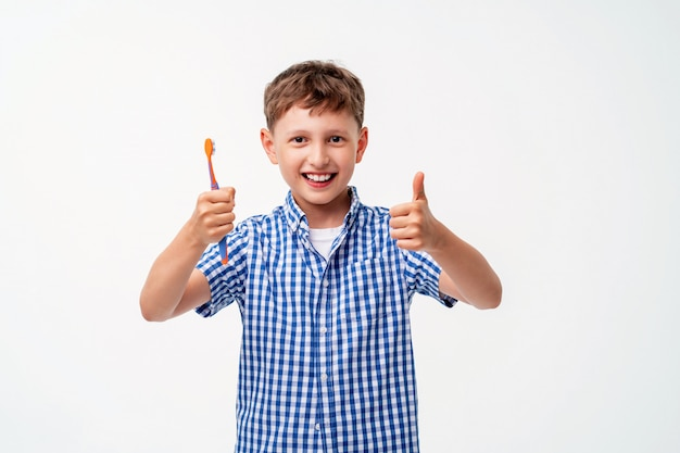 Szczęśliwy 7-letni chłopiec, uśmiechnięty, trzyma szczoteczkę do zębów
