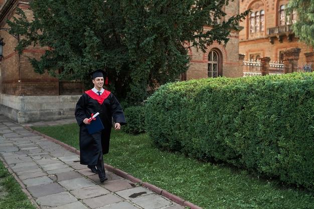 Szczęśliwy absolwent płci męskiej spacerujący po kampusie uniwersyteckim w szacie ukończenia szkoły