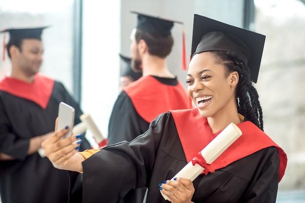 Szczęśliwy absolwent. uśmiechnięta dziewczyna w mortarboard robi selfie i wygląda szczęśliwy