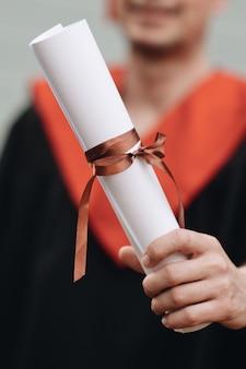 Szczęśliwy absolwent w sukni posiada dyplom ukończenia studiów
