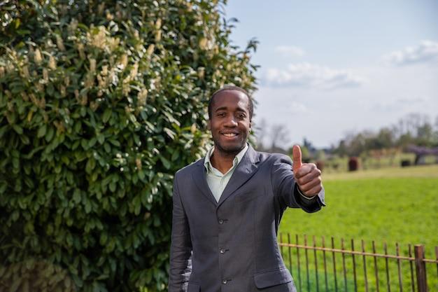 Szczęśliwy african american biznesmen sprawia, że uderzenie w górę gest na zewnątrz.