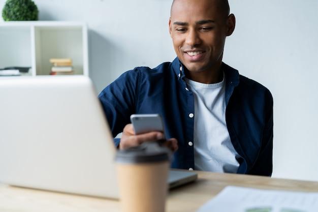 Szczęśliwy african american biznesmen za pomocą telefonu komórkowego w biurze.