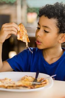 Szczęśliwy african american dzieciak jedzenie pizzy.
