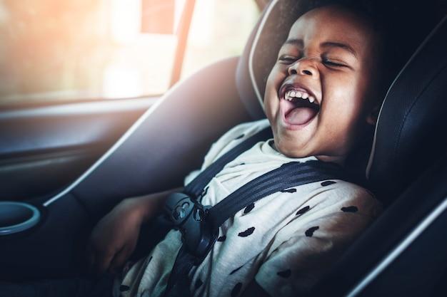 Szczęśliwy african american dzieciak w foteliku samochodowym