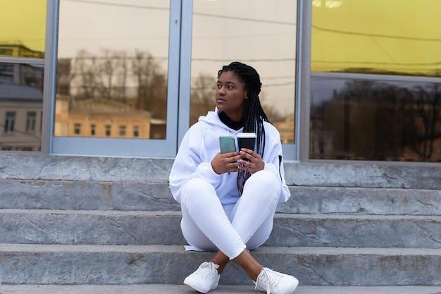 Szczęśliwy african american kobieta siedzi na schodach pięknego budynku