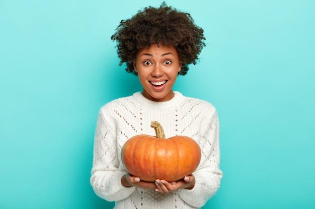 Szczęśliwy african american kobieta trzyma pomarańczową dynię, nosi biały sweter, uśmiecha się delikatnie, odizolowane na niebieskiej ścianie