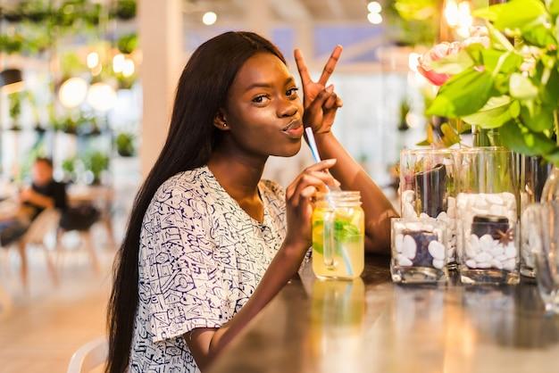 Szczęśliwy african-american kobieta ze szklanką naturalnej lemoniady w kawiarni. napój detoksykacyjny