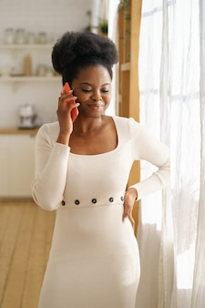 Szczęśliwy african american millennial kobieta nosić letnią sukienkę mody, rozmawiając przez telefon komórkowy w domu.