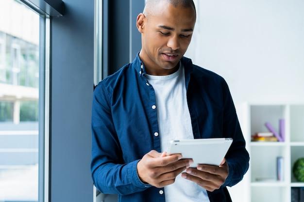Szczęśliwy african american przedsiębiorca przy użyciu komputera typu tablet.