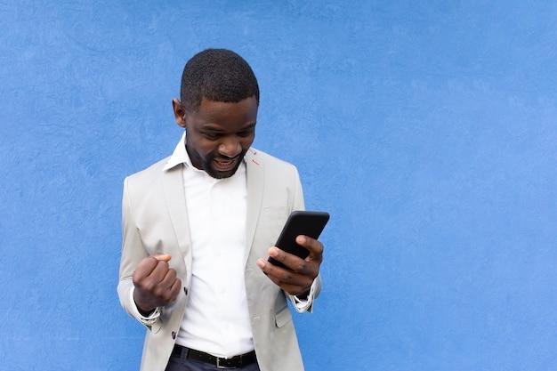 Szczęśliwy african american z telefonem na niebieskim tle