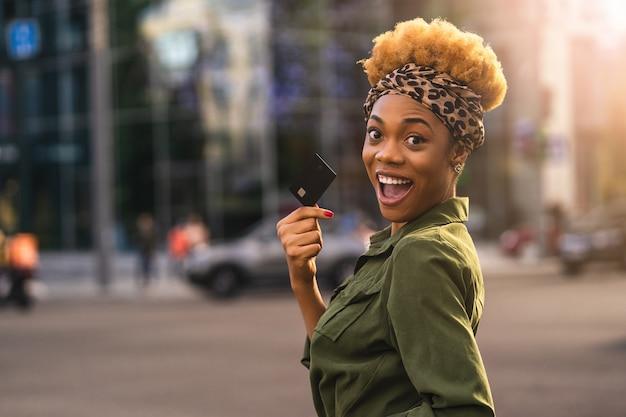 Szczęśliwy afro american piękna kobieta chodzenie po ulicy, trzymając kartę debetową