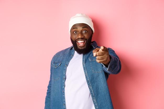 Szczęśliwy afro-amerykański hipster mężczyzna wskazujący palcem na aparat, potrzebuję cię, uśmiechnięty podekscytowany, stojący na różowym tle