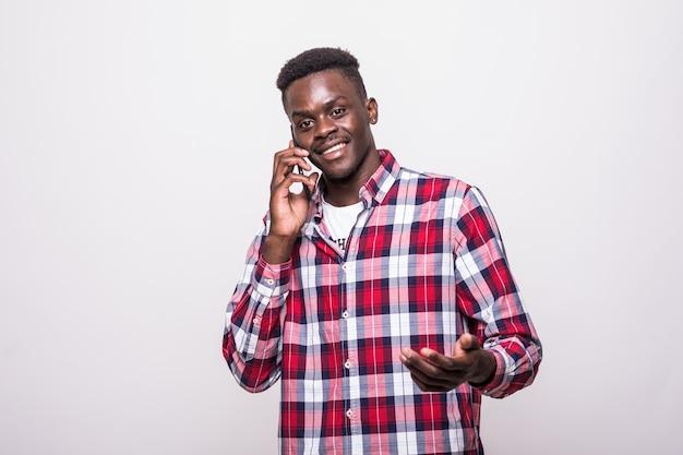 Szczęśliwy afro amerykański mężczyzna rozmawia przez telefon na białym tle