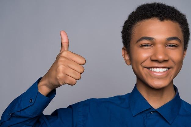 Szczęśliwy afro mężczyzna pokazuje kciuk up.