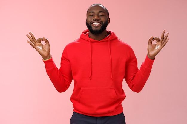 Szczęśliwy afroamerykanin brodaty mężczyzna w czerwonej bluzie z kapturem medytujący znalazł spokój nirwany uśmiechnięty zachwycony zamknij oczy zrelaksowany zrelaksowany stojący lotos mudra poza wyszukiwanie zen, praktyka jogi, różowe tło.