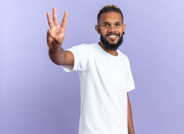 Szczęśliwy afroamerykanin młody człowiek w białej koszulce, patrząc na kamerę pokazującą i wskazującą w górę palcami numer trzy uśmiechnięty