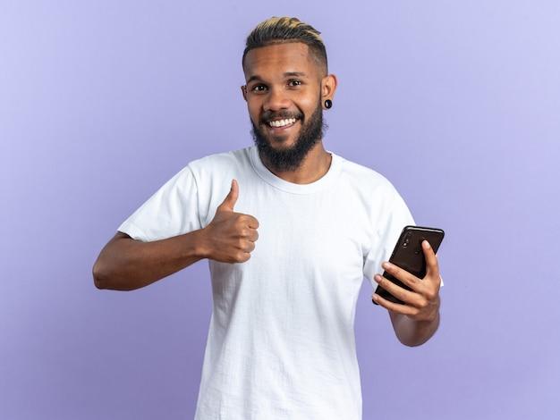 Szczęśliwy afroamerykanin młody człowiek w białej koszulce, trzymający smartfona