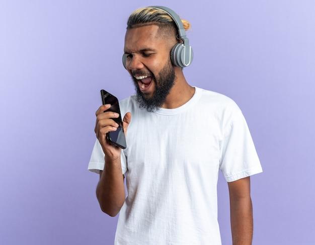 Szczęśliwy afroamerykanin młody człowiek w białej koszulce ze słuchawkami