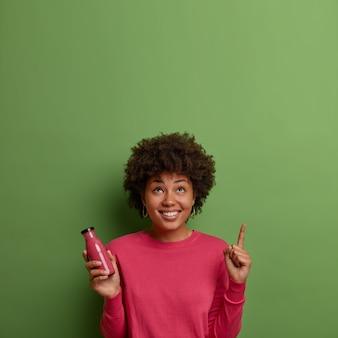 Szczęśliwy afroamerykanin pije koktajl ze świeżych owoców, trzyma w szklanej butelce napój z super żywności, wskazuje palcem wskazującym powyżej na zieloną ścianę, będąc w dobrym nastroju. zdrowy tryb życia